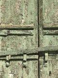 La struttura granulare di verde formidabile dell'esercito ha scheggiato la pittura e una maniglia su una vecchia porta in sole immagine stock libera da diritti