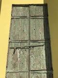 La struttura granulare di verde formidabile dell'esercito ha scheggiato la pittura su una vecchia porta al sole contrapposta da u immagini stock libere da diritti