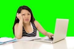 La studentessa abbastanza asiatica ha sovraccaricato sul suo computer portatile sulla chiave verde di croma dello schermo Fotografia Stock Libera da Diritti