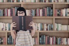 La studentessa asiatica ha letto il libro alla biblioteca Fotografia Stock