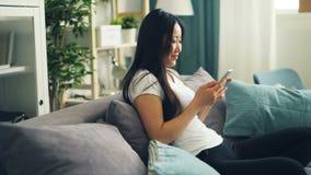 La studentessa asiatica sveglia sta usando lo schermo di contatto moderno dello smartphone e la seduta sorridente sul sofà a casa video d archivio