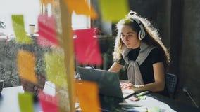 La studentessa attraente sta ascoltando musica con le cuffie che ballano e che cantano mentre lavorava con il computer portatile stock footage