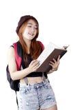 La studentessa castana legge il libro in studio Fotografia Stock