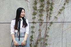 La studentessa che cinese della High School dell'Asia di bellezza adorabile il sorriso gode del tempo libero ha letto un libro Fotografie Stock Libere da Diritti