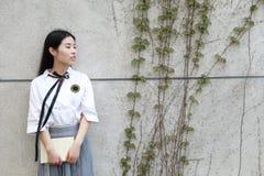 La studentessa che cinese della High School dell'Asia di bellezza adorabile il sorriso gode del tempo libero ha letto un libro Fotografia Stock Libera da Diritti