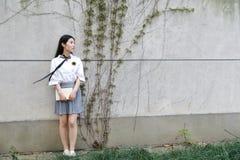 La studentessa che cinese della High School dell'Asia di bellezza adorabile il sorriso gode del tempo libero ha letto un libro Immagine Stock