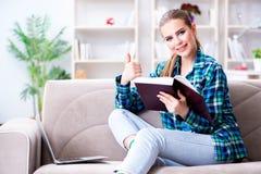 La studentessa che legge il libro che si siede sul sofà Immagini Stock Libere da Diritti