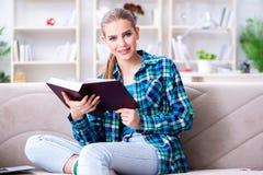 La studentessa che legge il libro che si siede sul sofà Fotografia Stock