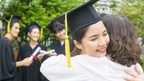 La studentessa con gli abiti di graduazione ed il cappello abbracciano il genitore dentro Fotografia Stock Libera da Diritti