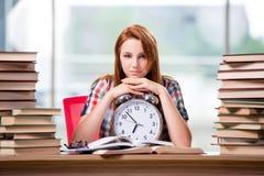 La studentessa con l'orologio che prepara per gli esami Fotografia Stock