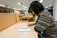 La studentessa di college tailandese sta scrivendo la sua nota del diario Fotografia Stock