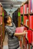 La studentessa di college tailandese sta selezionando il libro a partire dallo scaffale Immagini Stock