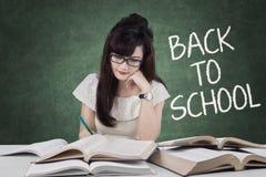 La studentessa di nuovo alla scuola e scrive sui libri Immagini Stock