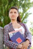 La studentessa esamina la distanza e tiene i suoi libri Fotografia Stock