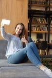La studentessa felice che si siede nella biblioteca fa il selfie Fotografia Stock