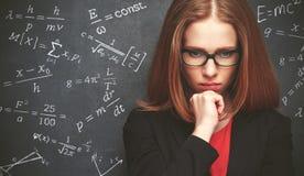 La studentessa, l'insegnante scrive sulla formula del gessetto per lavagna Immagine Stock