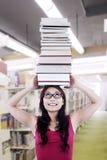 La studentessa porta i libri sulla testa Immagine Stock