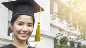 La studentessa sorride e tatto felice in abiti e cappuccio di graduazione Fotografia Stock Libera da Diritti