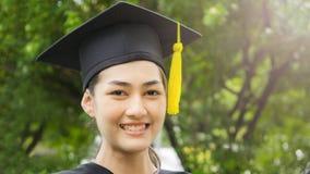 La studentessa sorride e tatto felice in abiti e cappuccio di graduazione Fotografia Stock