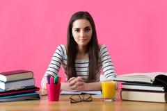 La studentessa sorridente che si siede al suo scrittorio ha riempito di manuali Fotografie Stock Libere da Diritti
