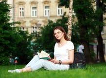 La studentessa sorridente in città parcheggia con il libro Immagini Stock Libere da Diritti
