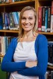 La studentessa sorridente con le armi ha attraversato nella biblioteca Immagine Stock Libera da Diritti