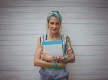La studentessa sta facendo una pausa la parete bianca con i taccuini in sue mani in attesa delle classi Ragazza moderna modello Fotografie Stock Libere da Diritti