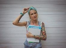La studentessa sta facendo una pausa la parete bianca con i taccuini in sue mani in attesa delle classi Ragazza moderna modello Immagini Stock Libere da Diritti