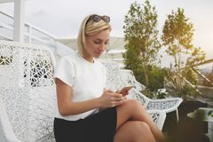 La studentessa sta guardando le foto sul telefono cellulare, mentre sta riposando in caffè dopo le conferenze Immagine Stock