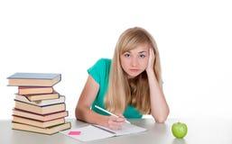 La studentessa stanca si siede alla tavola con i libri Immagine Stock