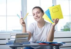 La studentessa teenager dell'adolescente piacevole sta sedendosi alla tavola con il fischio fotografie stock
