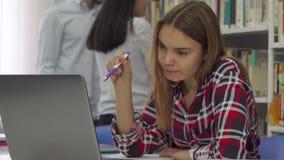 La studentessa tiene la penna nella sua bocca alla biblioteca fotografia stock