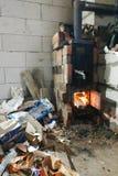 La stufa a legna brucia con le porte aperte in violazione della sicurezza e rappresenta una minaccia alla costruzione con il pote fotografie stock