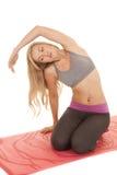 La stuoia rossa di yoga di allungamento della donna ha lasciato il braccio sopraelevato. immagine stock
