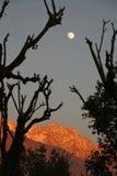 La subida de Fullmoon y la puesta del sol viva encendido snowpeaked adentro Foto de archivo