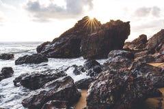 La subida del sol detrás del rock que creaba una estrella hermosa estalló efecto Fotos de archivo