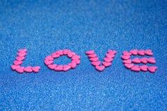 La sucrerie arrangent comme amour de mot sur le fond bleu Photos libres de droits