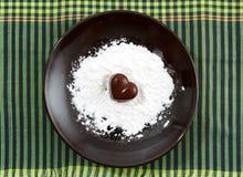La sucrerie en forme de coeur de chocolat d'un plat brun avec la poudre de sucre contre le vert a vérifié le fond de tissu Photos stock