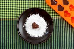 La sucrerie en forme de coeur de chocolat d'un plat brun avec la poudre de sucre et un bakin forment avec des chocolats contre le Images stock