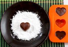 La sucrerie en forme de coeur de chocolat d'un plat brun avec la poudre de sucre et un bakin forment avec des chocolats contre le Image stock