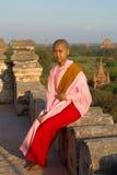 La suora birmana della ragazza-un sta sedendosi su un fondo delle tempie buddisti antiche di Bagan Fotografia Stock