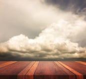 La superficie de madera marrón vacía de la tabla y la imagen de fondo borrosa cielo, para el montaje de la exhibición del product Foto de archivo