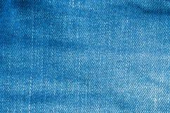 La superficie del primer de la tela azul vieja de los pantalones de la mezclilla texturizó el fondo imagen de archivo