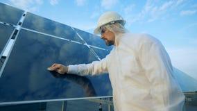 La superficie di una batteria solare sta ottenendo ispezionata e pulita da un tecnico di assistenza Concetto a energia solare video d archivio