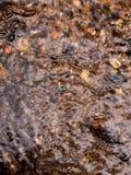 La superficie ondulada de la agua corriente con p natural multicolor Imágenes de archivo libres de regalías