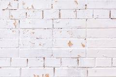 La superficie se pinta con la pintura blanca Una pared de los ladrillos de diversos tama?os Irregularidades, aspereza y peladura foto de archivo libre de regalías