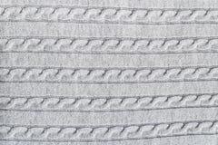 La superficie strutturata del tessuto tricottato grigio chiaro con il modello tradizionale della treccia per i progettisti purpos fotografia stock