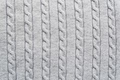 La superficie strutturata del tessuto tricottato grigio chiaro con il modello tradizionale della treccia per i progettisti purpos fotografia stock libera da diritti