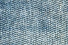 La surface de plan rapproché du vieux tissu de pantalons de blue-jean a donné au fond une consistance rugueuse Photo stock