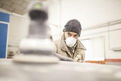 La surface de ponçage de voiture de peintre fonctionne dans l'atelier photo stock